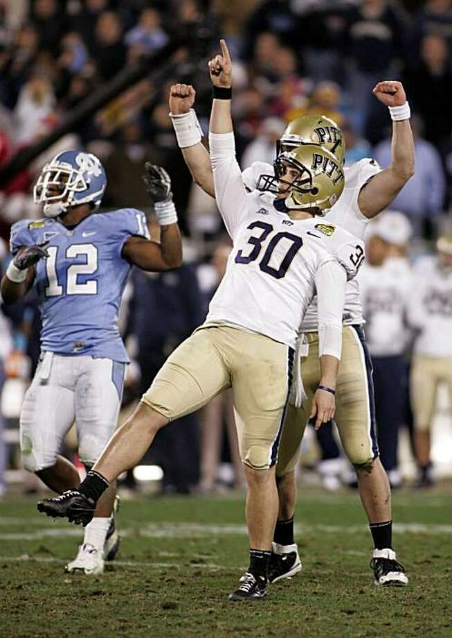 Pittsburgh kicker Dan Hutchins (30) reacts as North Carolina's Charles Brown (12) looks on after Hutchins' field goal during the final seconds of Pittsburgh's 19-17 win in the Meineke Bowl NCAA college football game in Charlotte, N.C., Saturday, Dec. 26, 2009. (AP Photo/Nell Redmond) Photo: Nell Redmond, AP