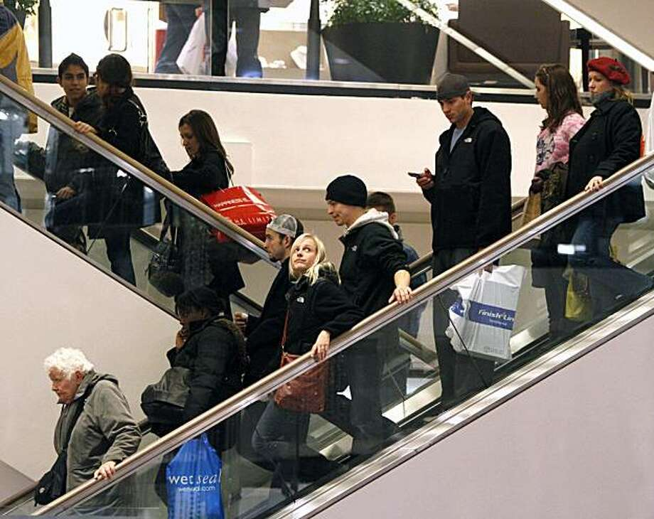 FILE - In this file photo made Dec. 19, 2009, shoppers ride escalators at Water Tower Place in Chicago.  Holiday shoppers spent a little more this season, according to data released Monday, Dec. 28, 2009,giving merchants some reason for cheer.(AP Photo/Jim Prisching, file) Photo: Jim Prisching, AP