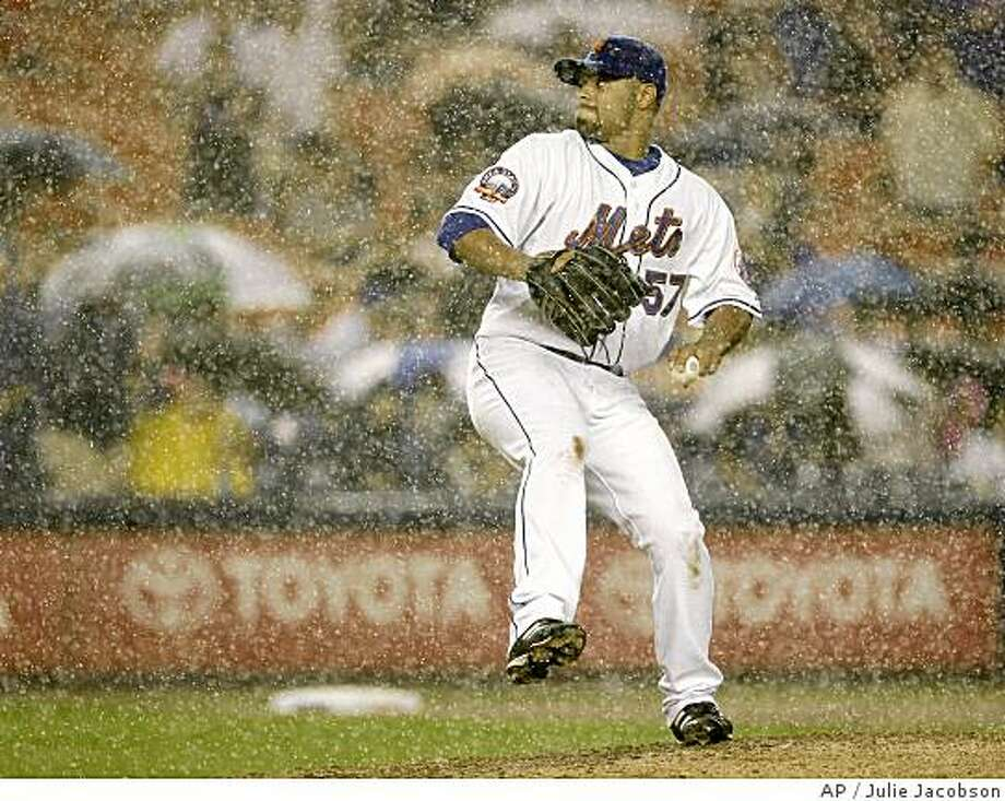 New York Mets pitcher Johan Santana delivers in a downpour against the San Francisco Giants during the fifth inning in Major League Baseball action Wednesday, July 9, 2008 at Shea Stadium in New York. (AP Photo/Julie Jacobson) Photo: Julie Jacobson, AP