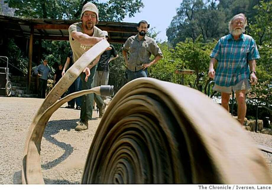 Johan Ostlund one of the volunteers that plans to stay and fight the fire practices rolling out a fire hose. Volunteers, staff and State and National firefighters have come to gather and pooled their talents and resources to save the Tassajara Zen Mountain Center from the advancing eastern flank of the Basin Complex Fire. Photographed in Carmel Valley July 9, 2008. By Lance Iversen / The Chronicle Photo: Iversen, Lance, The Chronicle