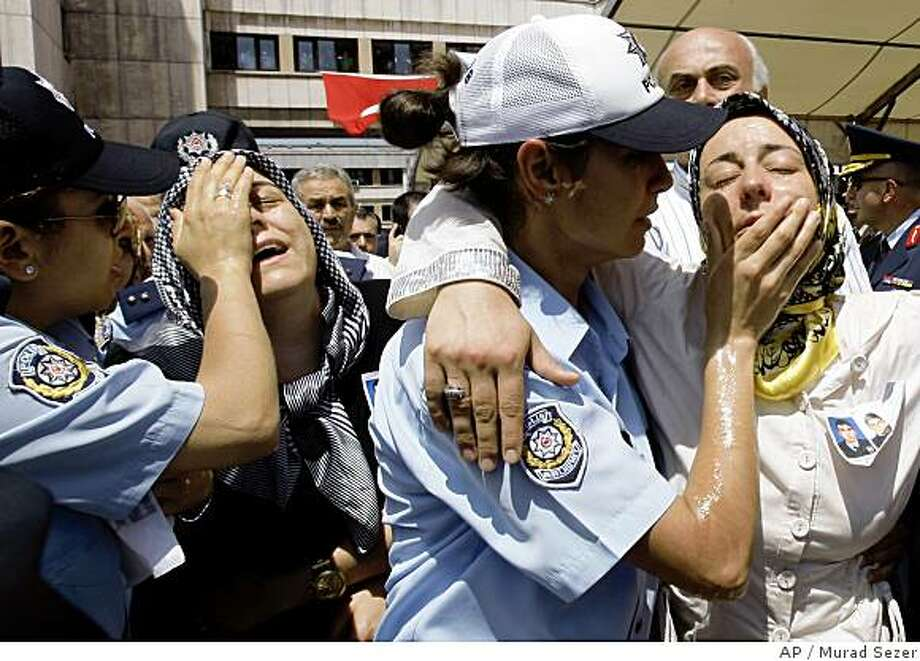 Relatives of the slain police officers are comforted by policewomen, during a ceremony at the police headquarters in Istanbul, Turkey,Thursday, July 10, 2008. An armed attack against the U.S. Consulate in Istanbul left three policemen and three assailants dead Wednesday. (AP Photo/Murad Sezer) Photo: Murad Sezer, AP
