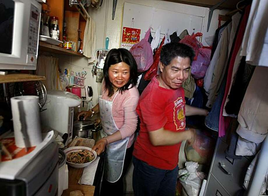 Lifen Deng (left) and Zhihua Mo squeeze through the entrance of their SRO while making the evening meal. Three generations of the Mo family have made their homes and lived their lives in small but tidy Chinatown SROs (single resident occupancy). Photo: Brant Ward, The Chronicle