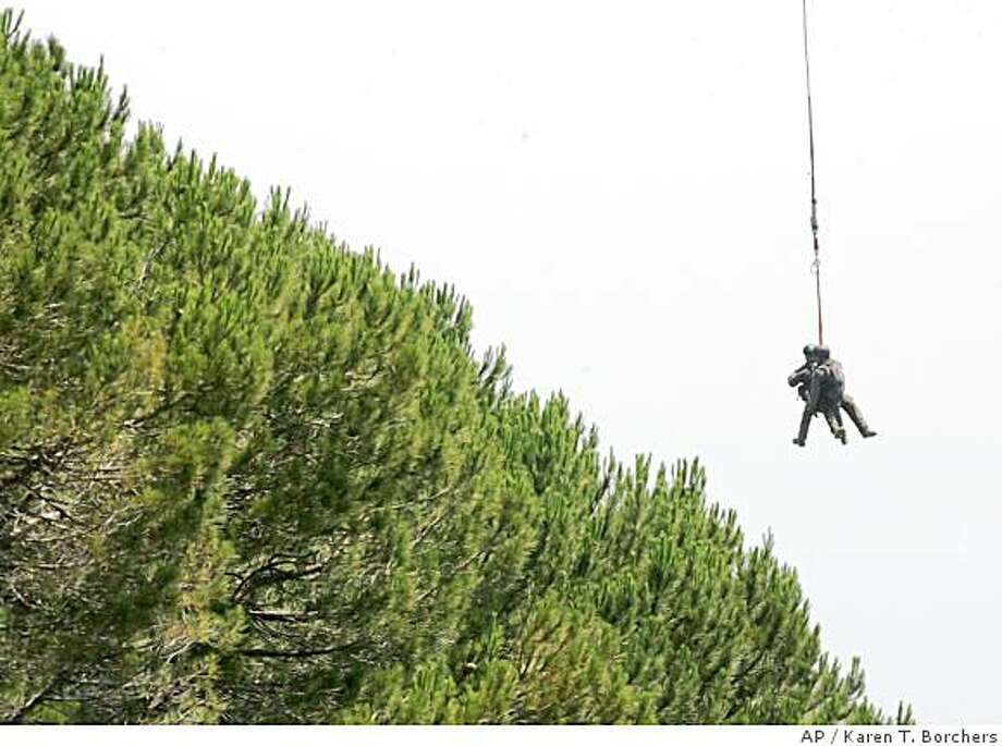Two SWAT team members are lifted out of the canyon from a rope from a helicopter over thick terrain above Saratoga, Calif., on Thursday, July 10, 2008.  Authorities killed an armed man and are searching for two others following a raid on an alleged marijuana garden in the Saratoga foothills. (AP Photo/The Mercury News, Karen T. Borchers) ** MAGS OUT, NO SALES ** Photo: Karen T. Borchers, AP