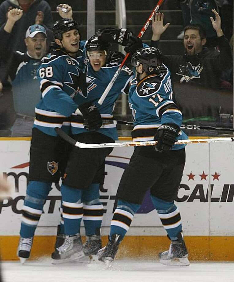 San Jose Sharks right wing Devin Setoguchi, center, celebrates with teammates Frazer McLaren, left, and Torrey Mitchell after scoring against the Phoenix Coyotes during the first period of an NHL hockey game in San Jose, Calif., Monday, Dec. 28, 2009. (AP Photo/Marcio Jose Sanchez) Photo: Marcio Jose Sanchez, AP