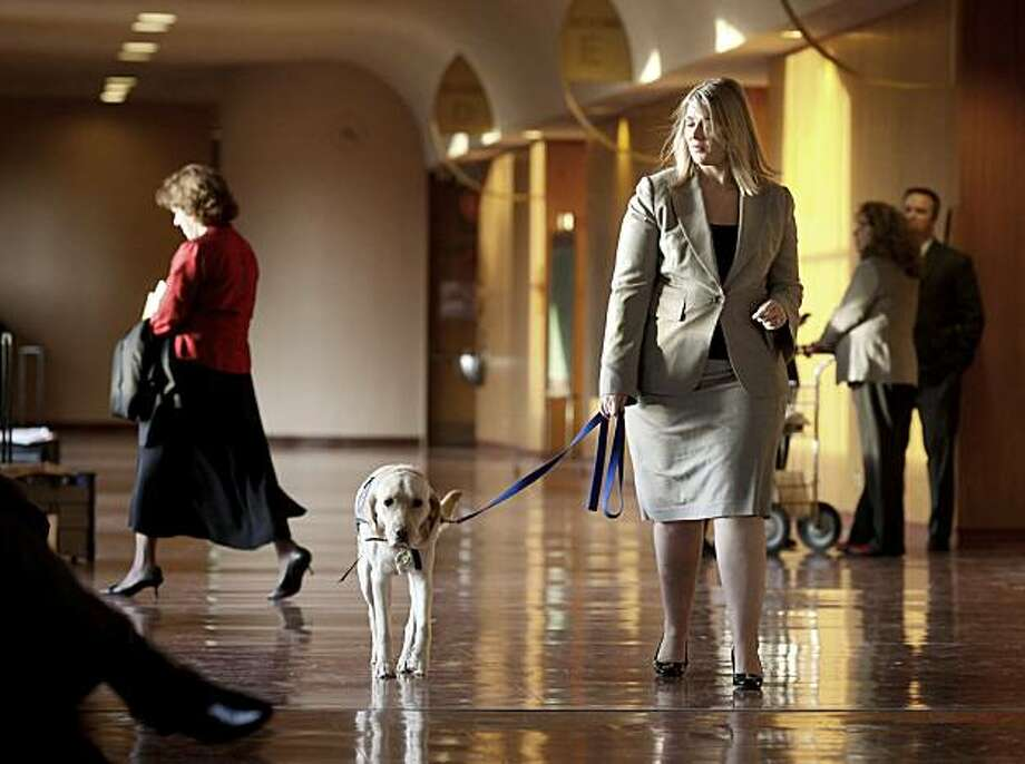 Buccine and Vivian walk past the court rooms in the Marin County Civic Center. Marin Deputy District Attorney Andrea Buccine uses her lab-golden retriever mix dog named Vivian in her work with crime victims and others to help break the ice. Photo: Brant Ward, The Chronicle