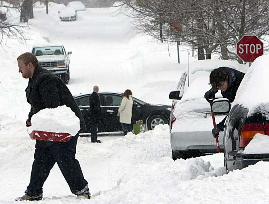 Jacob Longwell of St. Louis, left, and Josh Peterson of Fayetteville, Ark., right, try to dig a car out of a snow drift, in Omaha, Neb., Saturday, Dec. 26, 2009. Treacherous weather that has plagued much of the country for days stranded road and air travelers Saturday trying to get home after Christmas. (AP Photo/Nati Harnik) Photo: Nati Harnik, AP