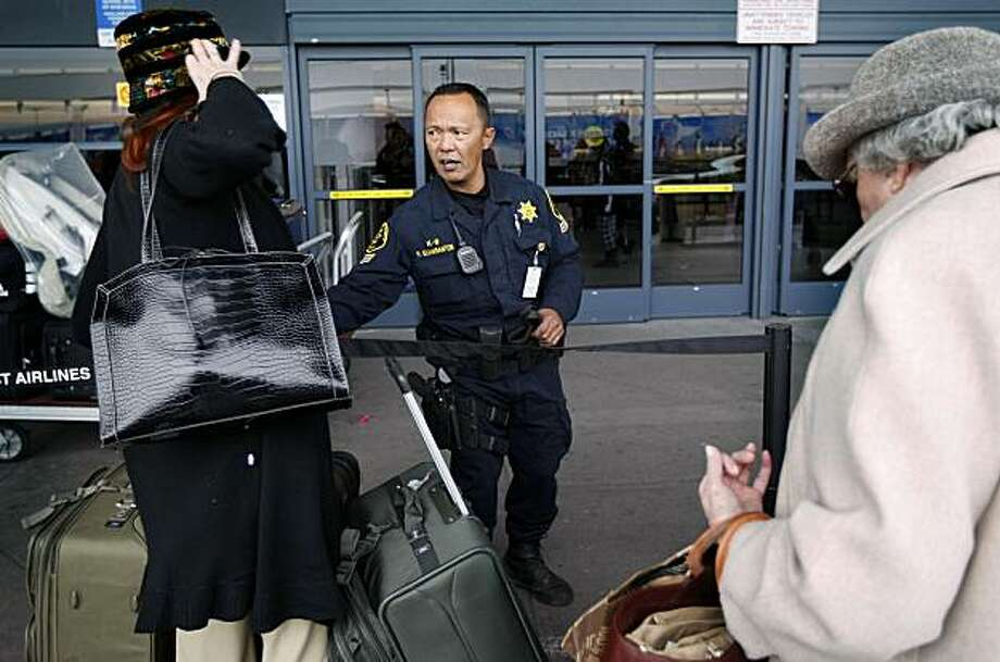 Ronaldo Eijansantos of the Alameda County Sheriffs Department keeps lines moving outside  terminal 2 at Oakland International Airport in Oakland,Ca. on Saturday December 26, 2009. Eijansantos said it was a regular scheduled shift for him at the airport today, a day after the attempted bombing of an airliner arriving into Detroit. Photo: Michael Macor, The Chronicle