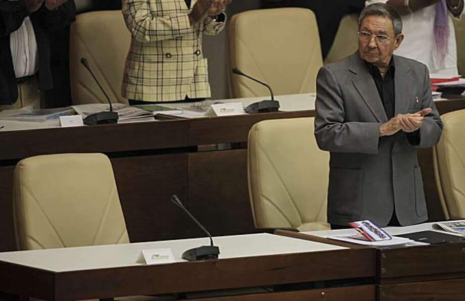Cuba's President Raul Castro applauds during the National Assembly's final plenary session in Havana, Sunday, Dec. 20, 2009. The empty seat belongs to his brother, former President Fidel Castro. (AP Photo/Ariana Cubillos) Photo: Ariana Cubillos, AP