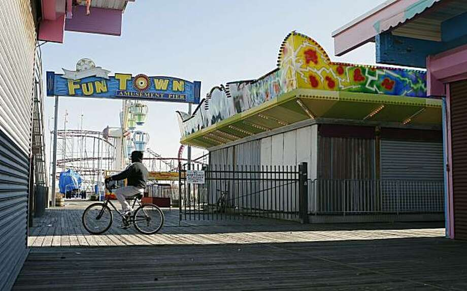 """A lone bicyclist rides on the boardwalk near an amusement pier Thursday, Dec. 17, 2009, in Seaside Heights, N.J. MTV's """"Jersey Shore,"""" takes place in this resort town, which is not only a setting but a state of mind in the show, which has been attracting outrage from one Italian-American group and turning its cast members into stars.  (AP Photo/Mel Evans) Photo: Mel Evans, AP"""