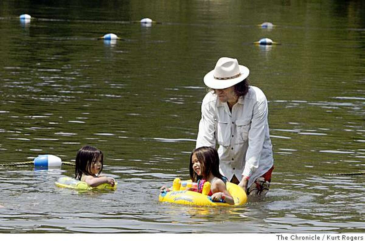 Jengiz Haas splashes around in the water at Lake Temescal with his kids Madison and Poinciana he likes to where a shirt and hat for full protection from the sun. on Wednesday, July 09 2008 in Oakland , Calif Photo by Kurt Rogers / The Chronicle.