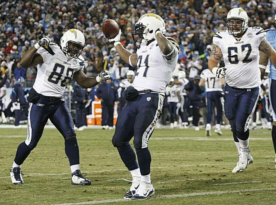 San Diego Chargers running back LaDainian Tomlinson (21) celebrates with tight end Kris Wilson (88) and guard Brandyn Dombrowski (62) after Tomlinson scored a touchdown on a 1-yard-run against the Tennessee Titans in the first quarter of an NFL football game on Friday, Dec. 25, 2009, in Nashville, Tenn. (AP Photo/Wade Payne) Photo: Wade Payne, AP