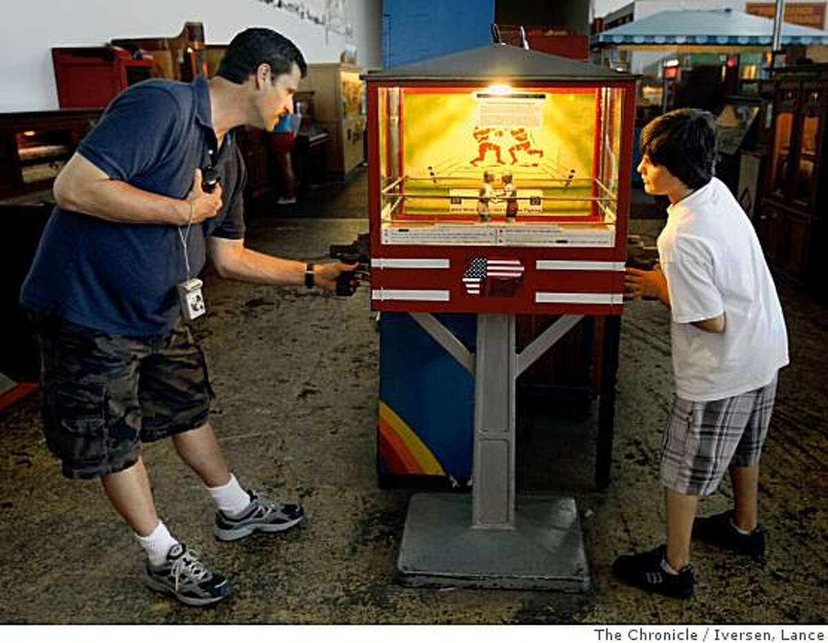 Craig Sussman and his son 11-year-old Armon both from Corona Calif., play a 1928 National Novelty Knock Out Fighters machine at Wusee Me Change at San Francisco's Warf. Alexander Rose, not in photo, is a self-described