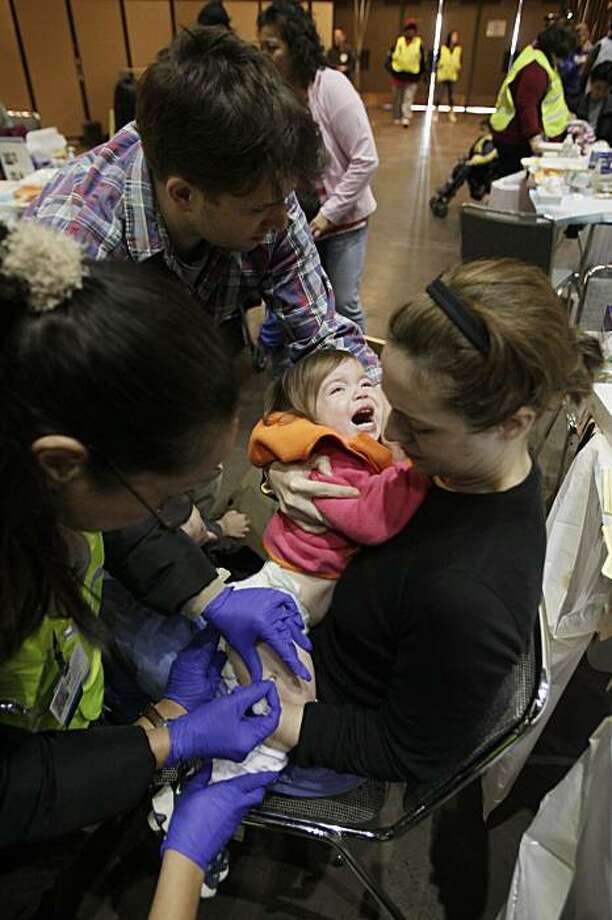 Lucy Jeffers, 1, receives a swine flu vaccine injection to her leg as her parents Crockett, top and Kate Jeffers hold her at the Bill Graham Civic Auditorium in San Francisco, Tuesday, Dec. 22, 2009. The city was administering 16,000 swine flu vaccinations Tuesday, the largest effort to date. (AP Photo/Marcio Jose Sanchez) Photo: Marcio Jose Sanchez, Associated Press