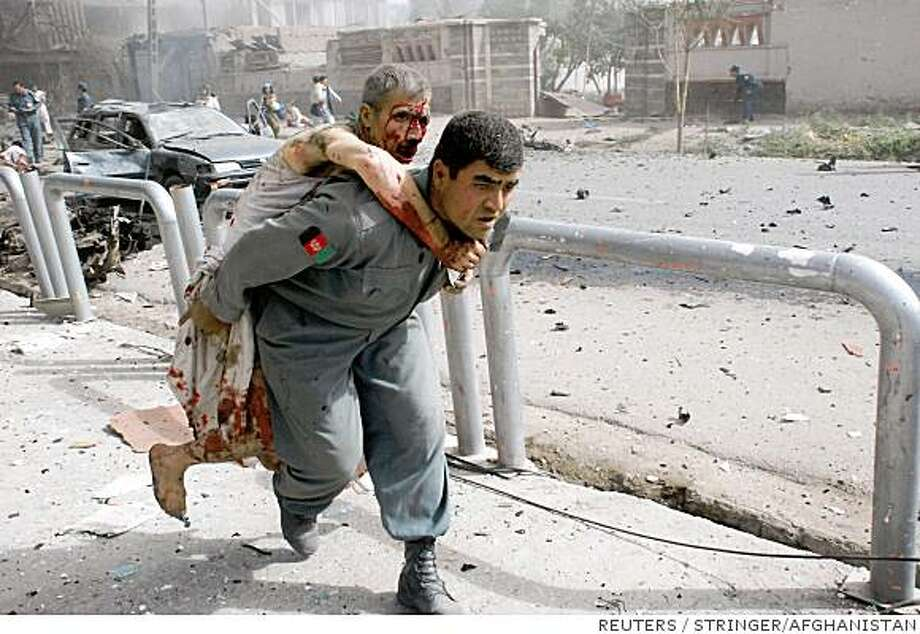 An Afghan policeman carries an injured man after a suicide attack on the Indian embassy in Kabul July 7, 2008. A Taliban suicide car bomb hit the Indian Embassy in Kabul on Monday, killing 41 people and wounding 139, in an attack Afghan authorities said was coordinated with foreign agents in the region, a likely reference to Pakistan. REUTERS/Pajwak News Agency (AFGHANISTAN) Photo: STRINGER/AFGHANISTAN, REUTERS