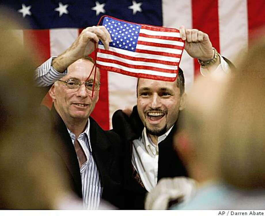 "Rescued American hostages Thomas R. Howes, left, and Marc D. Gonsalves wave an American flag in front of supporters and media at a ""Yellow Ribbon Ceremony"" where they spoke briefly to the press, Monday July 7, 2008, at Fort Sam Houston's Brooke Army Medical Center, in San Antonio, Texas. (AP Photo/Darren Abate) Photo: Darren Abate, AP"