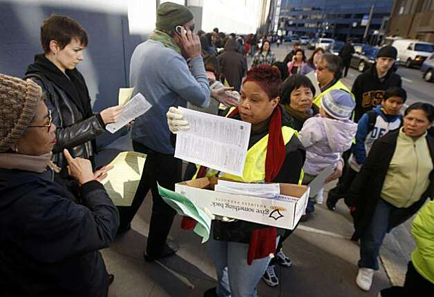 Erica McGary hands out applications to hundreds of people waiting in a line circling the Bill Graham Civic Auditorium for an H1N1 flu vaccination in San Francisco, Calif., on Tuesday, Dec. 22, 2009. Photo: Paul Chinn, The Chronicle