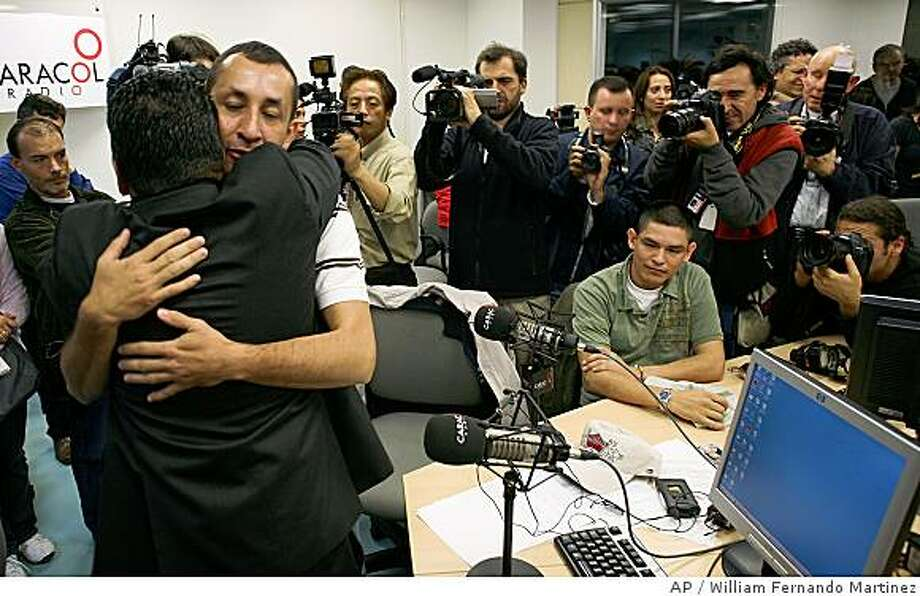 """Police captain Javier Rodriguez, left, embraces journalist Erwin Hoyos before sending a message to hostages at a studio of Caracol Radio station in Bogota, Sunday, July 6, 2008. Colombian police officers, freed Wednesday by Colombia's military after years held hostage by rebels of Revolutionary Armed Forces of Colombia, FARC, sent messages of hope to their fellow captives on a special radio program that is heard by many hostages in jungle camps. Former presidential candidate Ingrid Betancourt also made a surprise call to the program from France, saying se will """"continue fighting so that all of you return to freedom.""""(AP Photo/William Fernando Martinez) Photo: William Fernando Martinez, AP"""