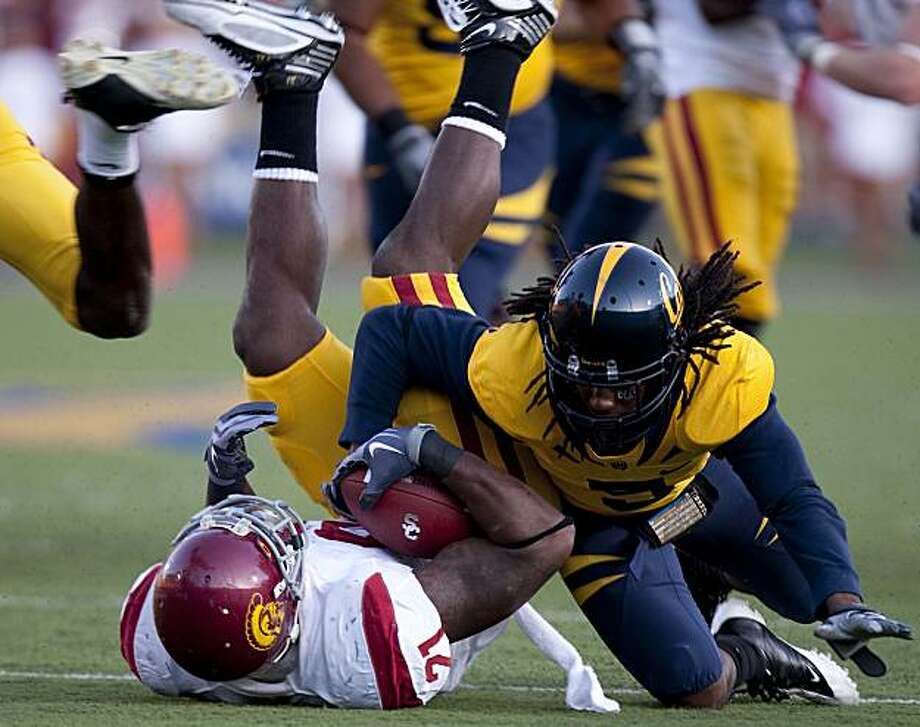 Tight end Allen Bradford (21) of the USC Trojans is tackles by cornerback Syd'quan Thompson (5) of the California Golden Bears during the second quarter at Memorial Stadium in Berkeley, Calif. on Saturday, Oct. 3, 2009. Photo: Stephen Lam, The Chronicle