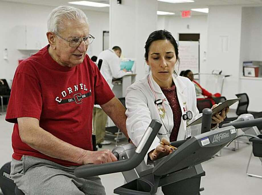 Cleveland Clinic exercise physiologist Audra DiRauso sets up an exercise bike for Anthony Rugare during a cardiac rehabilitation class Monday, Dec. 21, 2009, in Cleveland. Researchers found people who completed all 36 sessions of cardiac rehabilitation that Medicare covers were less likely to die or suffer a heart attack in the following three to four years. (AP Photo/Mark Duncan) Photo: Mark Duncan, AP