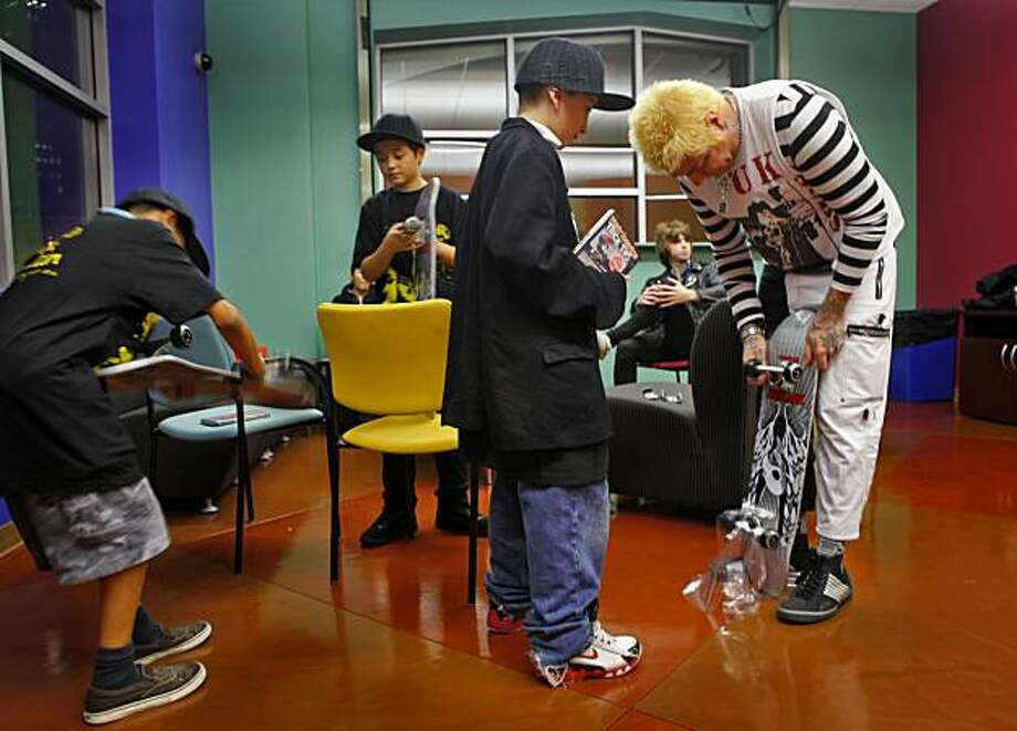 Lars Frederiksen helps Steven Asencio peels off the plastic wrapper from the new  Tony Hawk skateboards, Monday Dec.21, 2009, at the Tenth and Mission Family Shelter in San Francisco, Calif. Photo: Lacy Atkins, The Chronicle
