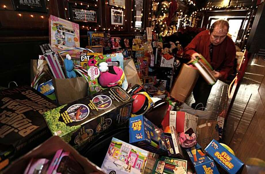 Host Lefty O'Doul's bar, manager John Fair stacks Christmas ghifts during the San Francisco Firefighters ninth annual last-second toy drive near Union Square, in San Francisco,Ca. on Thursday December 24, 2009. Photo: Michael Macor, The Chronicle