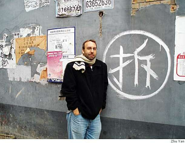 "Michael Meyer before the symbol ""chai"" (raze) that adorns Beijing homes slated for destruction. Photo: Zhu Yan"