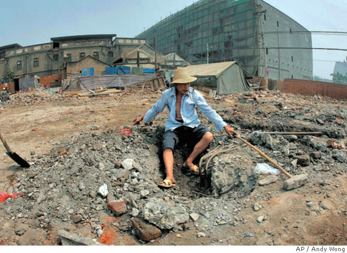 A migrant workerat the demolition site of the Qianmen hutong, one of the historic neighborhoods disappearing from Beijing to make room for development. Associated Press photo by Andy Wong
