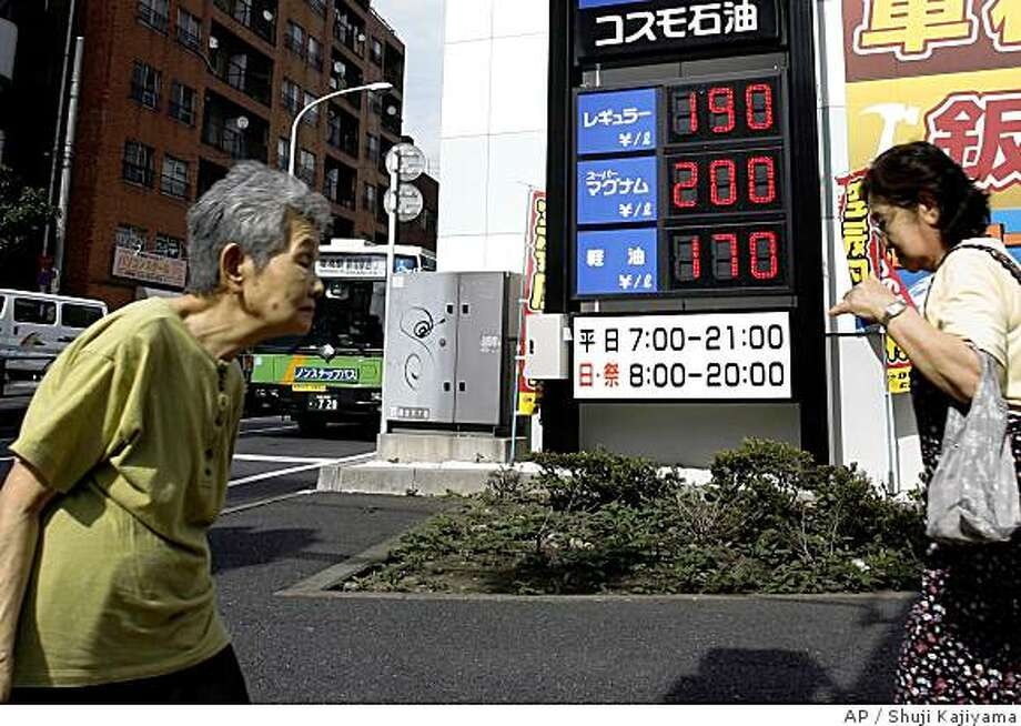 Passersby walk past a price board indicating regular gas is sold at 190 yen (US$1.79) per liter (0.26 gallon) and the high-octane gas at 200 yen ($1.88) per liter at a gas station in Tokyo Thursday, July 3, 2008. Between surging oil prices, food inflation and a credit crunch that's depressed global growth, leaders from the Group of Eight economic powers face the gravest combination of economic woes in at least a decade when they gather next week. (AP Photo/Shuji Kajiyama) Photo: Shuji Kajiyama, AP