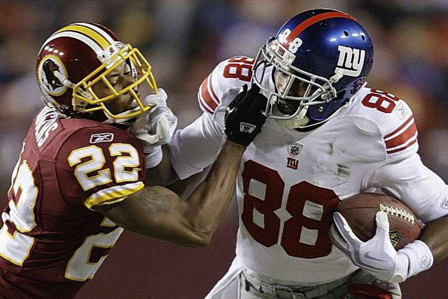 Washington Redskins cornerback Carlos Rogers and New York Giants wide receiver Hakeem Nicks grab each other's face mask during the first quarter of an NFL football game, Monday, Dec. 21, 2009, in Landover, Md. (AP Photo/Alex Brandon) Photo: Alex Brandon, AP