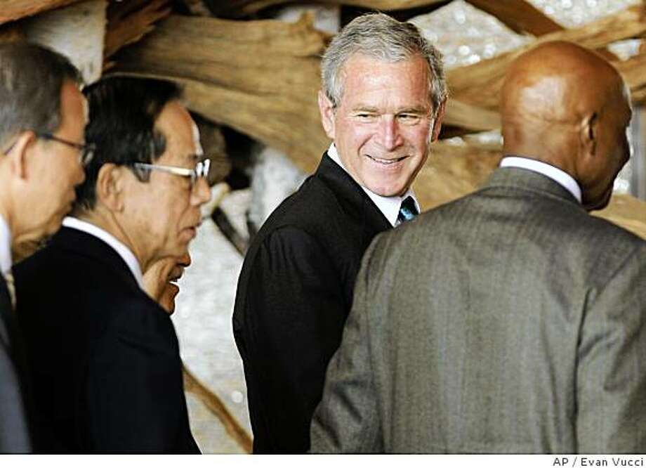 U.S. President George W. Bush, second from right, looks back at Japanese Prime Minister Yasuo Fukuda, second from left, after a group photo with African Outreach leaders at the G-8 summit on Monday, July 7, 2008 in the lakeside resort of Toyako on Japan's northern main island of Hokkaido. (AP Photo/Evan Vucci) Photo: Evan Vucci, AP