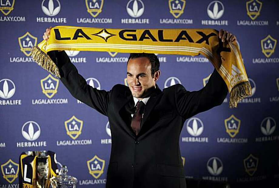 Los Angeles Galaxy captain Landon Donovan holds up a Galaxy scarf during a soccer news conference in Los Angeles on Wednesday, Dec. 16, 2009. The Galaxy announced Wednesday that it has signed Donovan to a new four-year contract and that he will be allowed to pursue opportunities to join a foreign club on a short-term loan agreement. (AP Photo/Damian Dovarganes) Photo: Damian Dovarganes, AP