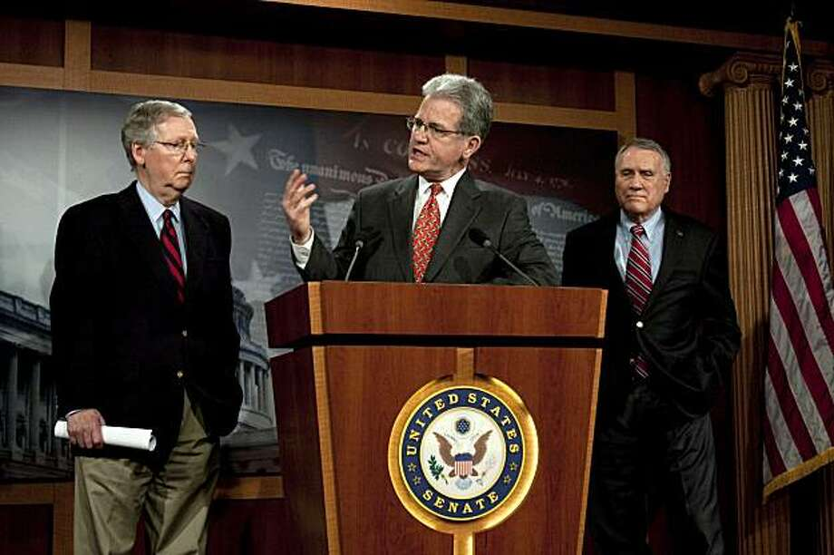 Sen. Tom Coburn, R-Okla., speaks at a news conference about the pending health care bill as Senate Minority Leader Mitch McConnell, R-Ky., left, and Sen. Jon Kyl, R-Ariz., listen on Capitol Hill in Washington, Sunday, Dec. 20, 2009.(AP Photo/Harry Hamburg) Photo: Harry Hamburg, AP