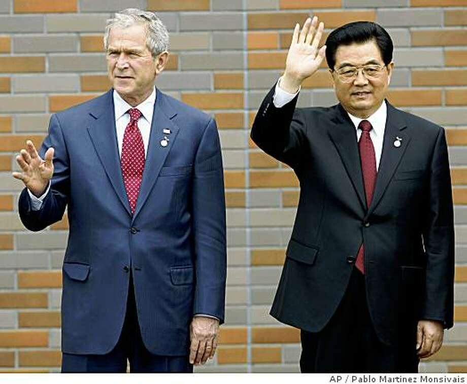 US President George W. Bush, left, and Chinese President Hu Jintao, right, wave as they pose for a group photo for the G8 leaders and Major Economic outreach leaders  Wednesday, July 9, 2008 in the lakeside resort of Toyako on Japan's northern island of Hokkaido. (AP Photo/Pablo Martinez Monsivais) Photo: Pablo Martinez Monsivais, AP