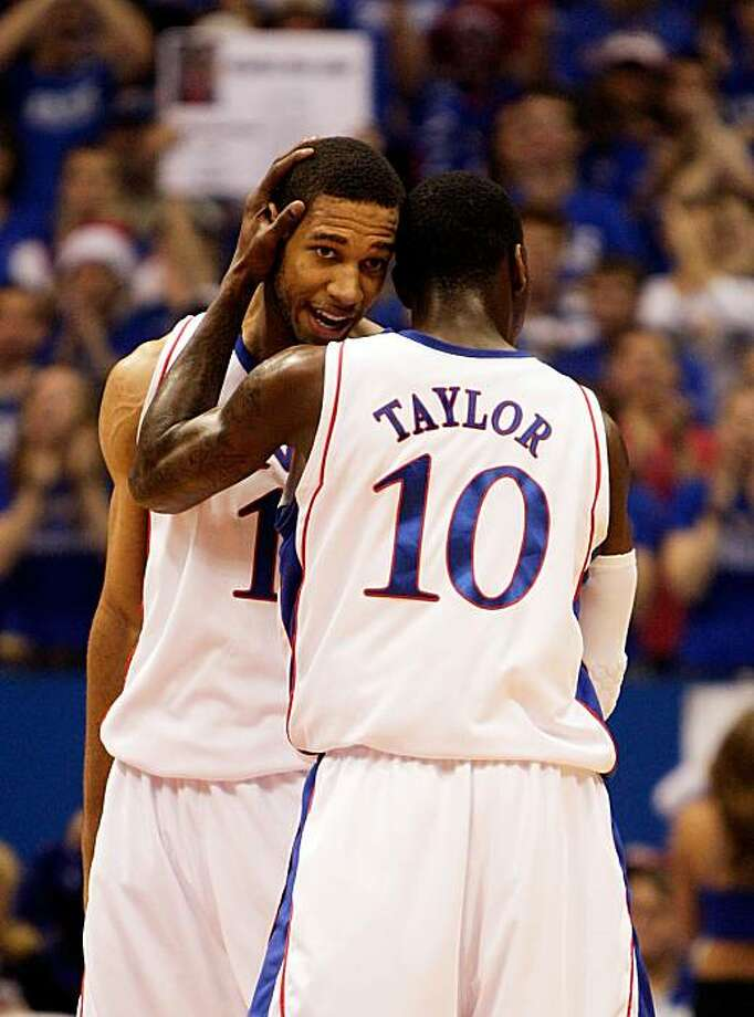 LAWRENCE, KS - DECEMBER 19:  Tyshawn Taylor #10 of the Kansas Jayhawks hugs Xavier Henry #1 after Henry sank a three-pointer during the game against the Mighigan Wolverines on December 19, 2009 at Allen Fieldhouse in Lawrence, Kansas.  (Photo by Jamie Squire/Getty Images) Photo: Jamie Squire, Getty Images
