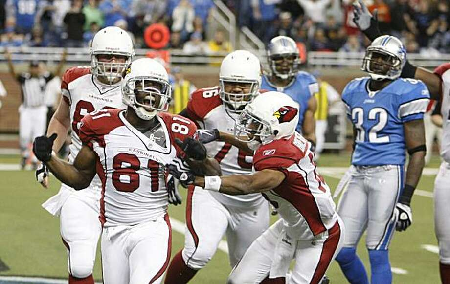 Arizona Cardinals wide receiver Anquan Boldin (81) is congratulated by teammates after scoring a touchdown as the Cardinals defeat the Detroit Lions in the closing minutes during an NFL football game at Ford Field in Detroit, Sunday, Dec. 20, 2009. At far right is Detroit Lions cornerback Anthony Henry (32). (AP Photo/Carlos Osorio) Photo: Carlos Osorio, AP