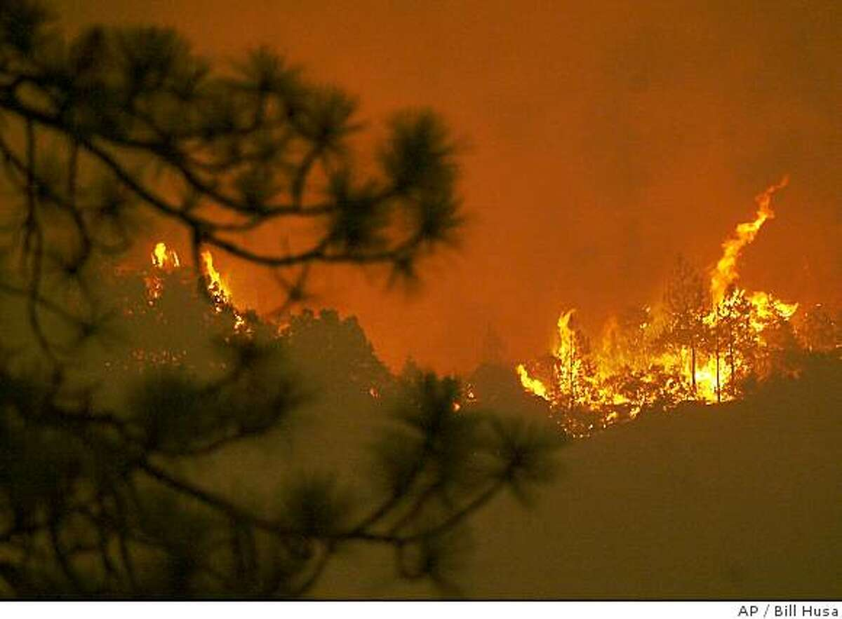 Flames rise up from across the canyon seen from Dean Rd. in Paradise, Calif. Tuesday, July 8, 2008. The fire is working it's way down the other side of the canyon across the West Branch of the Feather River from Dean Rd. (AP Photo/Chico Enterprise-Record), Bill Husa)