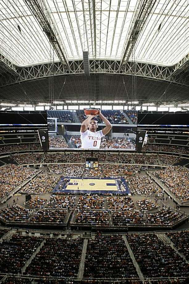 Texas guard Avery Bradley (0) is shown on the large video board as fans look on in the first half of an NCAA college basketball game, Saturday, Dec. 19, 2009, in Arlington, Texas.  Texas won the first basketball game played in Cowboys Stadium, the venue that will host the NBA All-Star game in February. (AP Photo/Tony Gutierrez) Photo: Tony Gutierrez, AP