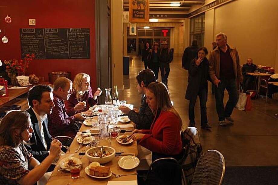 Diners, who all agreed that they don't mind eating in a hallway near the bathroom and the building exit as long as the food is good and they are with friends, enjoy an evening dinner II Cane Rosso in the Ferry Plaza on Friday, Dec. 18, 2009 in San Francisco, Calif. Photo: Mike Kepka, The Chronicle