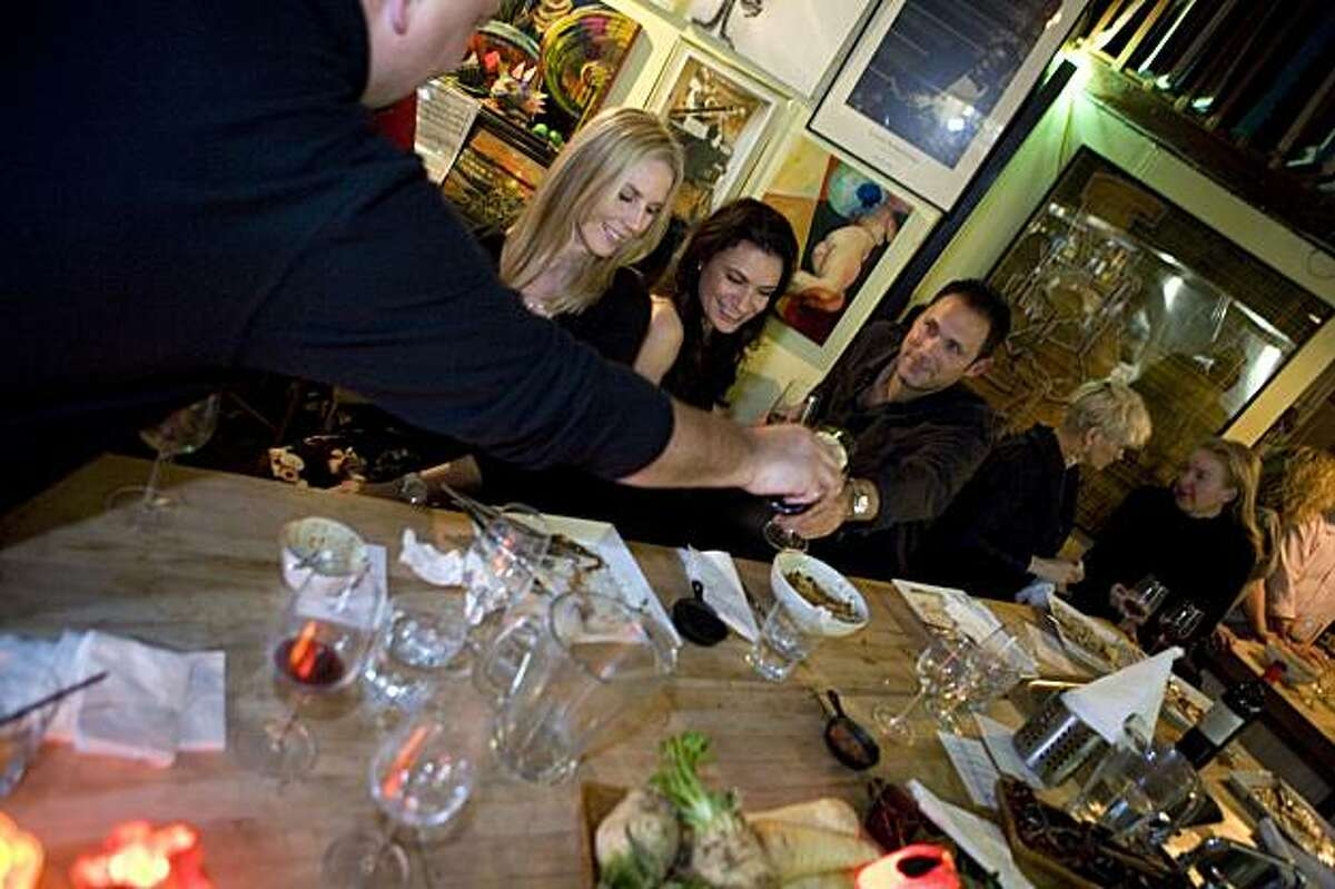 Mind Your Tongue business partner Kai Schoenhals, left, pours wine for guests, Emily Reid, Jennifer Belardi, and Shaun Waldowski, while Kai's wife, Kasia Figura and guest Tanya Fleischer chat during diner in a hidden room behind a dive bar in San Francisco, Calif. on Thursday, December 17, 2009. Kat Wade / Special to the Chronicle