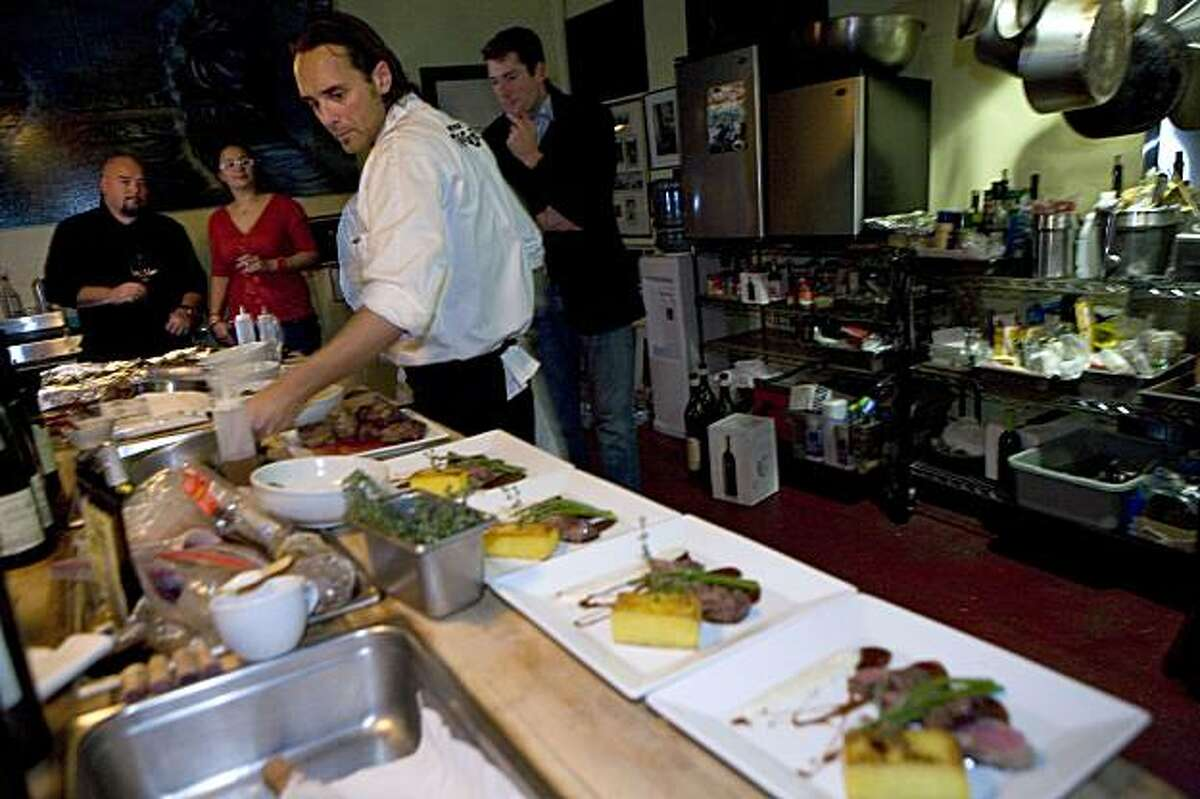 While Mind Your Tongue business partner Kai Schoenhals, left, and guests, Chandini Davis and Ryan Bedel, right, mingle in the kitchen, chef, Daniel Isberg plates the main course for diners in San Francisco, Calif. on Thursday, December 17, 2009. With the inception of concepts such as Mind Your Tongue, fine dining served family style in a back room behind a dive bar or in a soon-to-be mobile restaurant, the restaurant scene in the Bay Area is reinventing itself with this warm deviation from the traditional white-tablecloth experience. Kat Wade / Special to the Chronicle