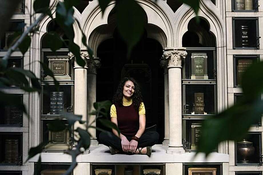 Kimberly Johansson, curator at Johansson Projects, an art gallery in Oakland, sits amongst incased urns in the columbarium at the Chapel of the Chimes in Piedmont Monday, November 23, 2009. Photo: Erin Lubin, Special To The Chronicle