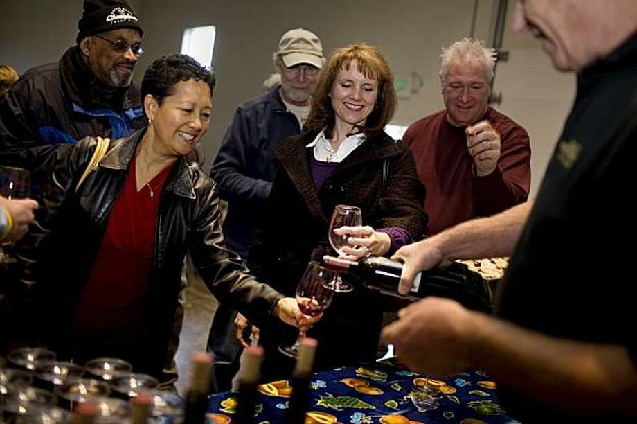 Owner Mike Milat, right, pours a 2006 Merlot for Joy Gutierrez, of Benicia, left, and Linda Pauline, of Oakley, center, at Milat Winery, a family-owned and operated winery, in St. Helena, Ca., on Saturday, Dec. 5, 2009. Production is limited to about 3500 cases of estate-grown, produced, and bottled wine. Photo: Lianne Milton, Special To The Chronicle