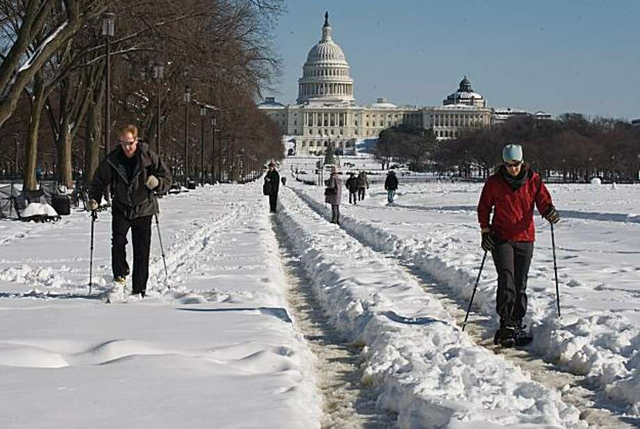 People use skis and snow shoes on the National Mall near the US Capitol in Washington on December 20, 2009. A ferocious snow storm blanketed much of the eastern United States, cutting power to hundreds of thousands of homes, paralyzing air traffic and stranding motorists. The governors of Virginia, Maryland, West Virginia and Delaware declared states of emergency in advance of the storm, the worst to hit the region in decades.           AFP PHOTO/Nicholas KAMM (Photo credit should read NICHOLAS KAMM/AFP/Getty Images) Photo: Nicholas Kamm, AFP/Getty Images