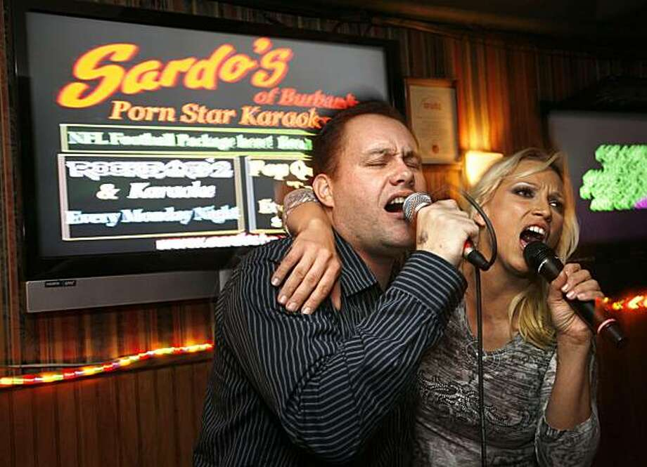 "Daniel Hogan of Los Angeles, left, and adult entertainer Nicki Hunter sing together during Porn Star Karaoke at Sardo's Grill and Lounge in Burbank, Calif. on Tuesday, Nov. 17, 2009. Hogan says he enjoys coming because people are not too uptight. ""It gives normal people a chance to get a little wilder than they normally would."" (AP Photo/Jason Redmond) Photo: Jason Redmond, AP"