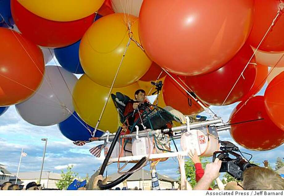 Kent Couch lifts off from his gas station in Bend, Ore., in his lawn chair rigged with more than 150 giant party balloons, Saturday, July 5, 2008. Couch, 48, is making his third cluster balloon flight and hopes to go more than 200 miles to Idaho before running out of daylight or helium. (AP Photo/Jeff Barnard) Photo: Jeff Barnard, Associated Press