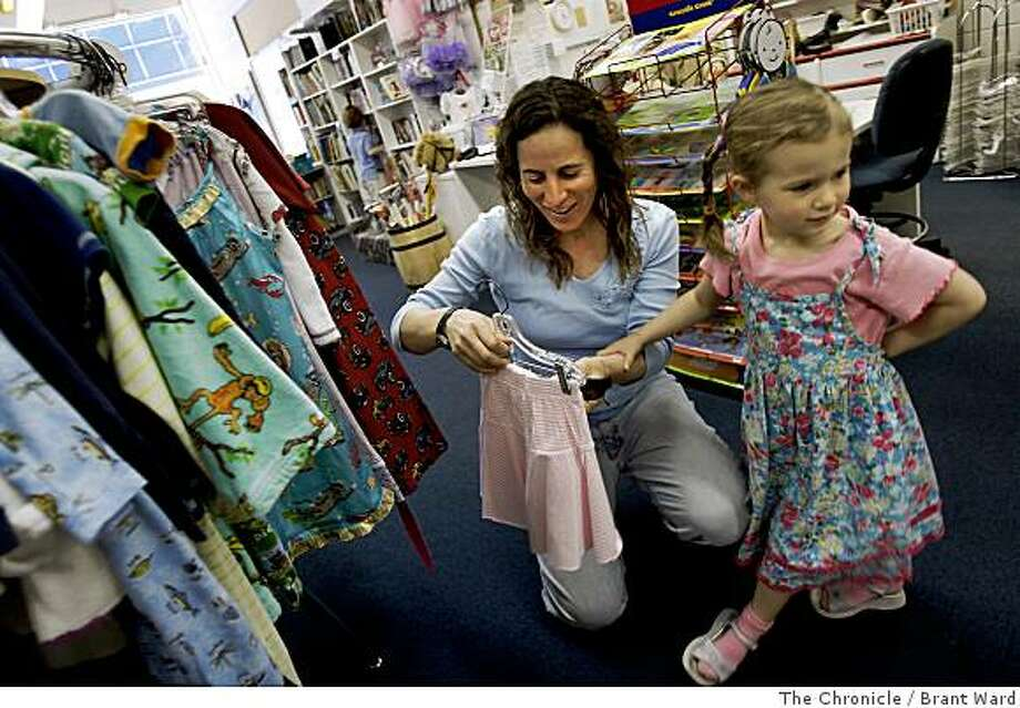 "Amy Allen, left, and her daughter Kyra check out the clothes at Play It Again. Amy Allen never buys any new present for her kids to give to other kids at birthday parties, as a way of reducing consumption and being green. She is shopping at ""Play It Again"" in San Rafael, Calif. May 28, 2008. Photo: Brant Ward, The Chronicle"