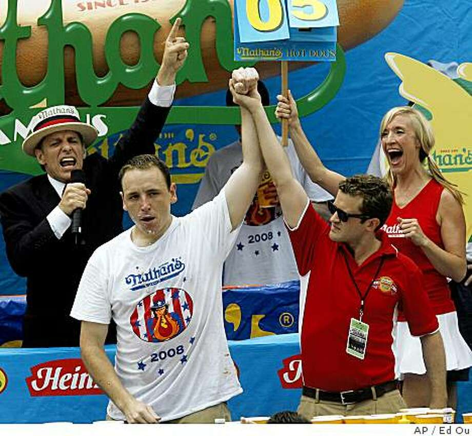 Joey Chestnut is declared the winner of the annual hot dog eating contest, Friday July 4, 2008, in the Brooklyn borough of New York. Joey Chestnut reclaimed the top spot at the annual hot dog eating contest in Coney Island on Friday after first tying with archrival Takeru Kobayashi with 59 hot dogs in a 10-minute chow-down and then beating him in a five-dog eat-off. (AP Photo/Ed Ou) Photo: Ed Ou, AP