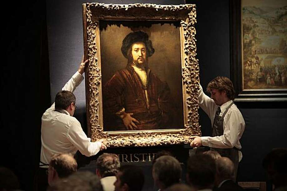 "Christies auction house employees carry the Rembrant masterpiece ""Portrait of a Man with Arms Akimbo"" into the room where it is to be auctioned in King Street showroom, on December 8, 2009 in London. The auction house is hope bids will reach £18million (19,935,000 Euros),  £20.2 million including fees, the highest price ever reached for a Rembrandt painting. AFP PHOTO / Carl Court. (Photo credit should read Carl Court/AFP/Getty Images) Photo: Carl Court, AFP/Getty Images"