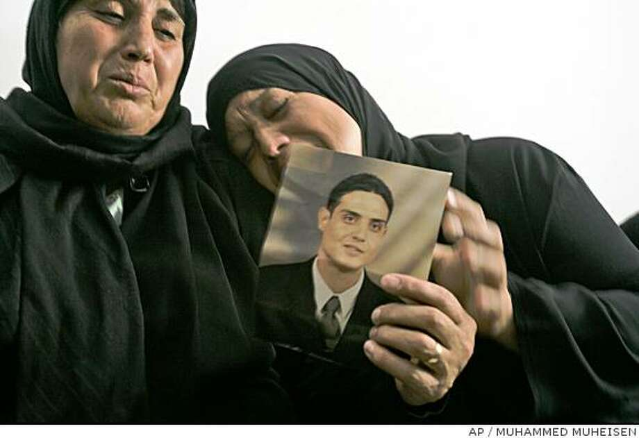 ** CORRECTS ATTACKER'S NAME AND AGE ** Palestinian Sarah Dwayat, right, reacts as she holds a portrait of her son Hussam Dwayat, 30, who carried out yesterday's attack in Jerusalem, at the family house in the east Jerusalem neighborhood of Tsur Baher, Thursday, July 3, 2008. Dwayat plowed an enormous construction vehicle into cars, buses and pedestrians on a busy street Wednesday, killing three people and wounding at least 45 before he was shot dead by security officers. (AP Photo/Muhammed Muheisen) Photo: MUHAMMED MUHEISEN, AP