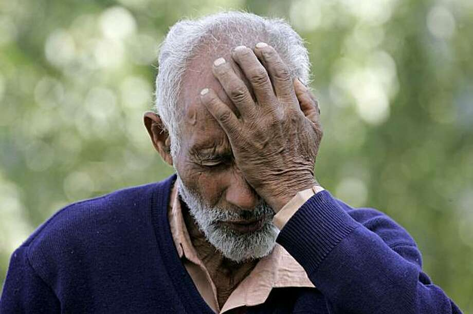 **ADVANCE FOR MONDAY, DEC. 7** In this photo taken Oct. 7, 2009 in Bimyar, about 60 miles (100 kilometers) west of Srinagar, India, Kashmiri farmer Atta Mohammed, 70, gestures as he speaks to the Associated Press at a graveyard where he says he has helped bury 235 unidentified dead. Human rights workers say that in the past 18 months they have identified dozens of burial grounds where they believe Indian security forces dumped more than 2,400 corpses. In a region struggling to emerge from two decades of violence that has left 68,000 people dead, the graveyards have deeply shaken Kashmir, digging up memories of the estimated 10,000 people who disappeared at the height of the fighting. (AP Photo/Mukhtar Khan) Photo: Mukhtar Khan, AP